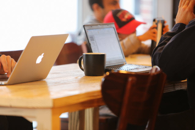 People working and playing at a coffee shop table