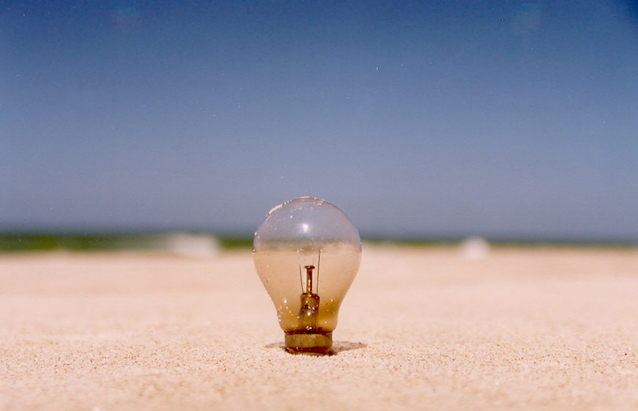 Light bulb propped up on a sandy beach