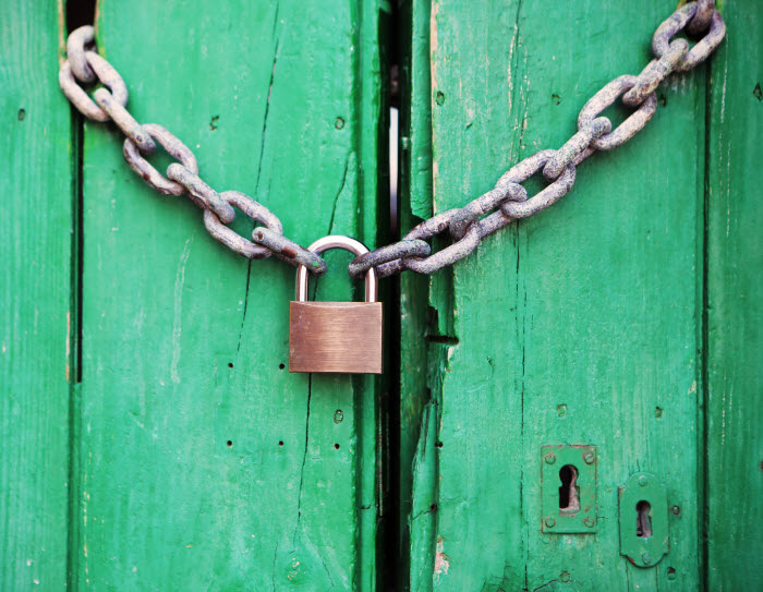 Lock holding chain closure of green wooden doors