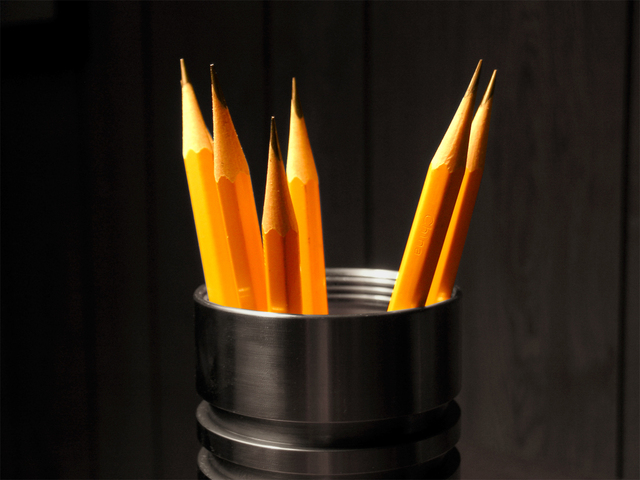 Gray cup holding six freshly sharpened pencils