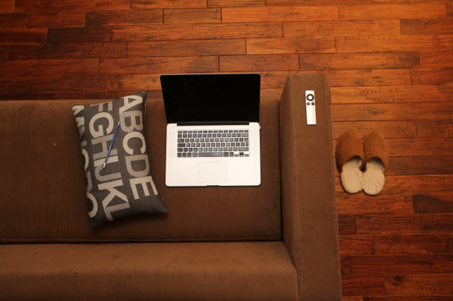 Top view of laptop, alphabet pillow, remote control, and slippers on a brown couch