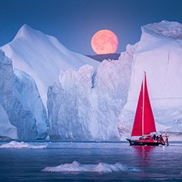 Red Sailboats in front of full moon in Greenland