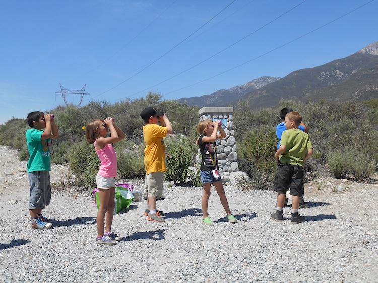 Young children looking through binoculars in a desert landscape