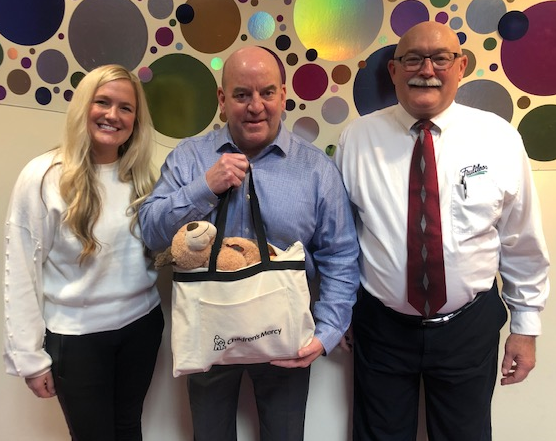 Faultless Healthcare Linen's (left to right) Jesse Geisel, Mark Spence and Jack Jester with one of Children's Mercy comfort care bags the company sponsored, given to children in foster care filled with comfort items and to carry their personal belongings.