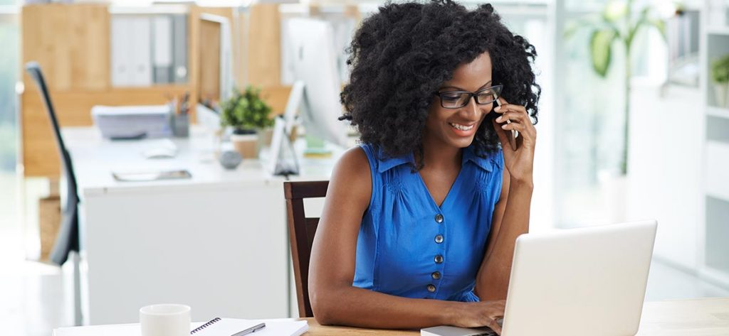 Cheerful business lady talking on the phone when using laptop