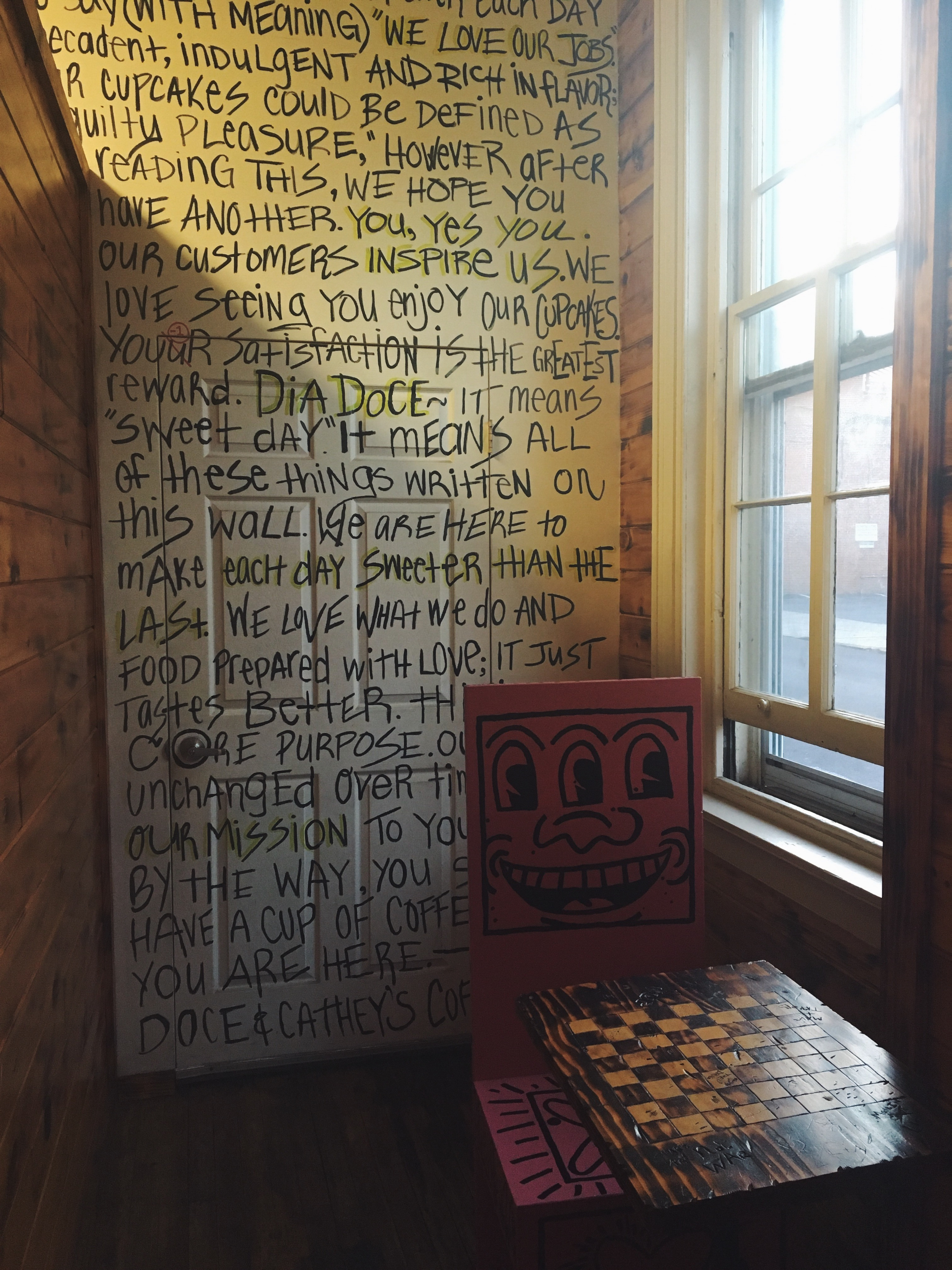 West Chester study spots: a smiling chair sits in front of a word-filled wall inside the coffee and cupcake shop Dia Doce, located on High Street