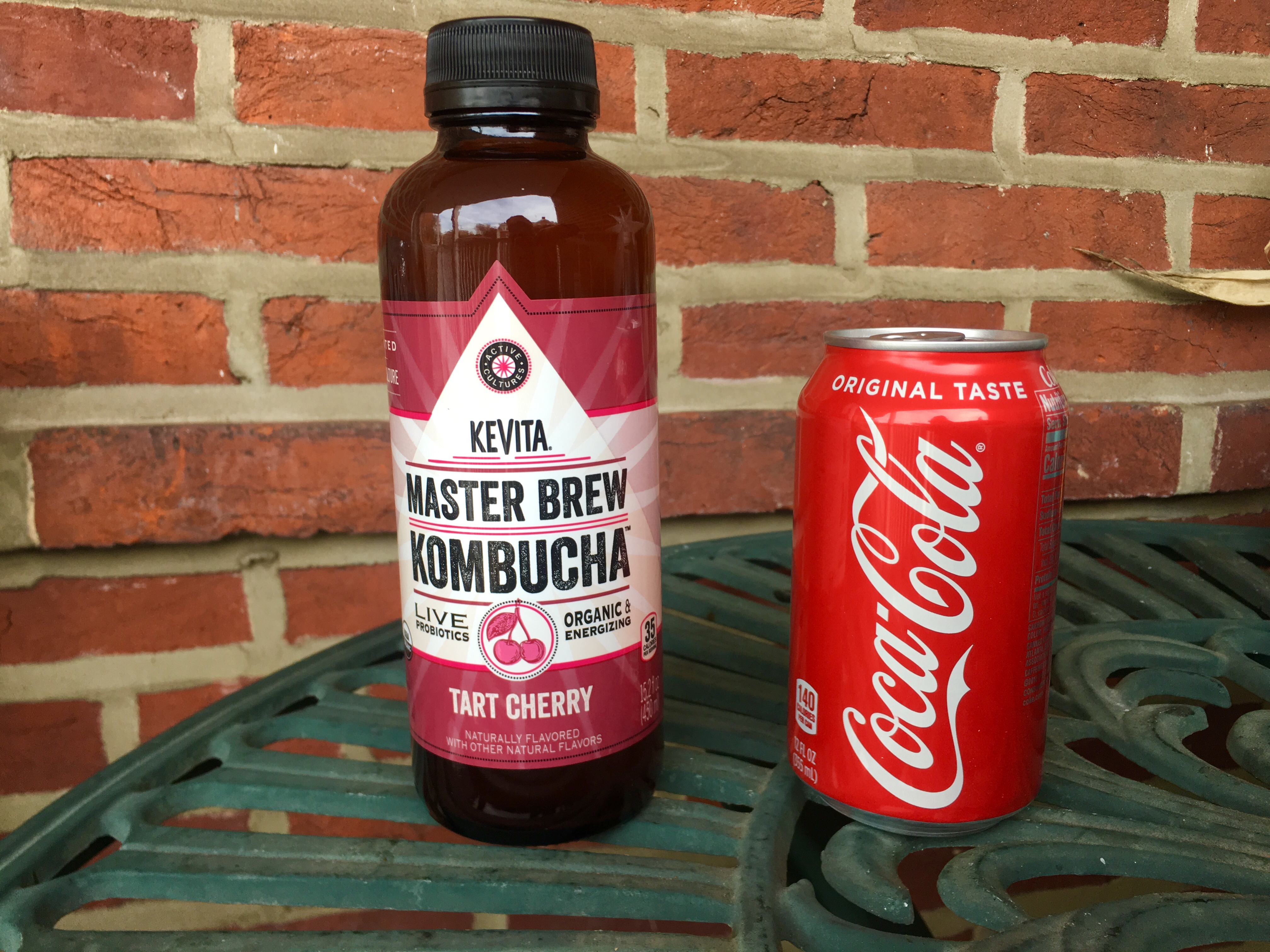 Kombucha bottle next to a can of coke