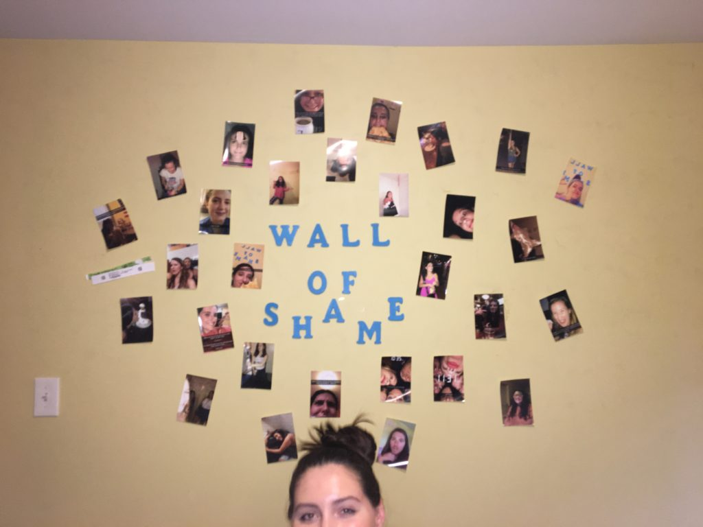 roommate under a wall covered with memorable pictures from final year of college