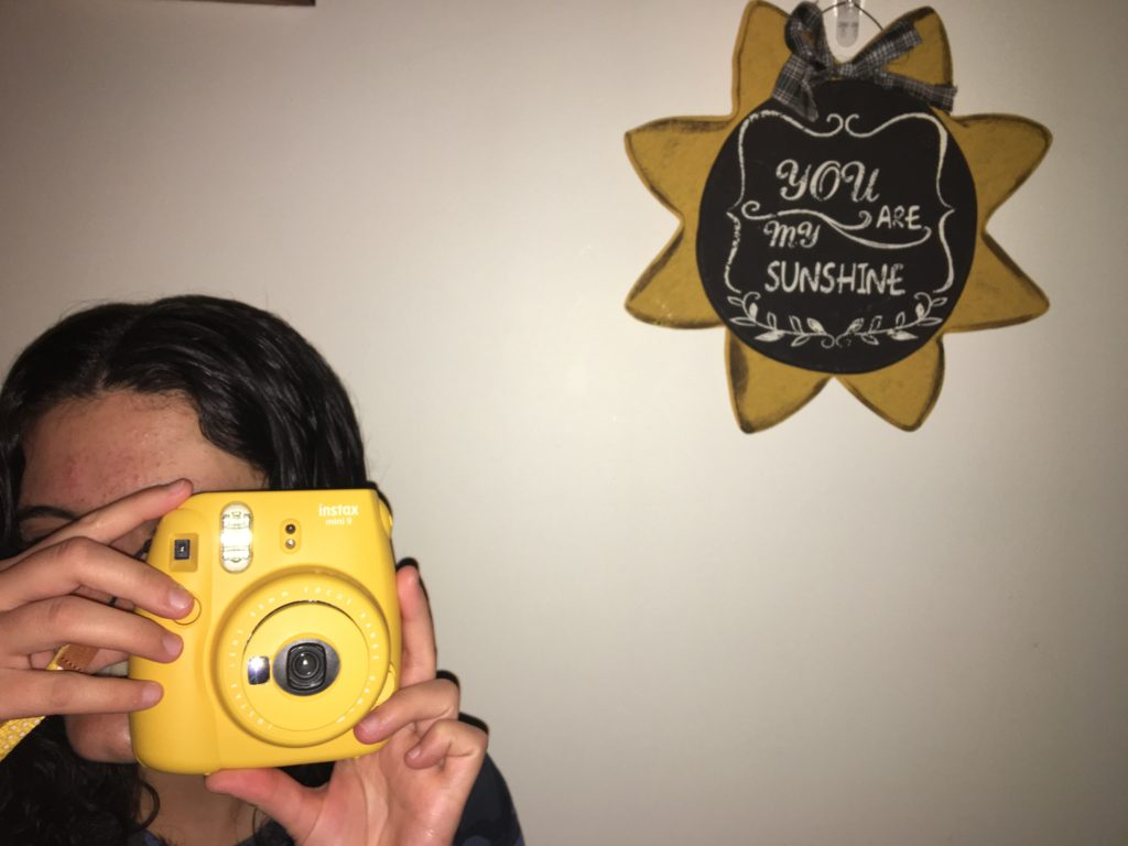 girl taking photo with yellow camera to capture final year of college