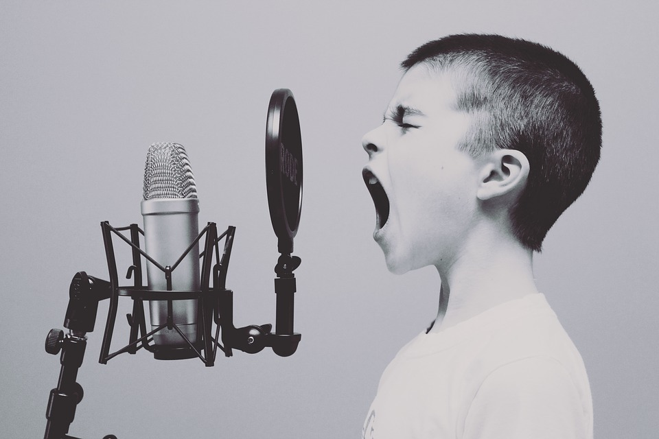 Young boy singing into microphone. change your mind