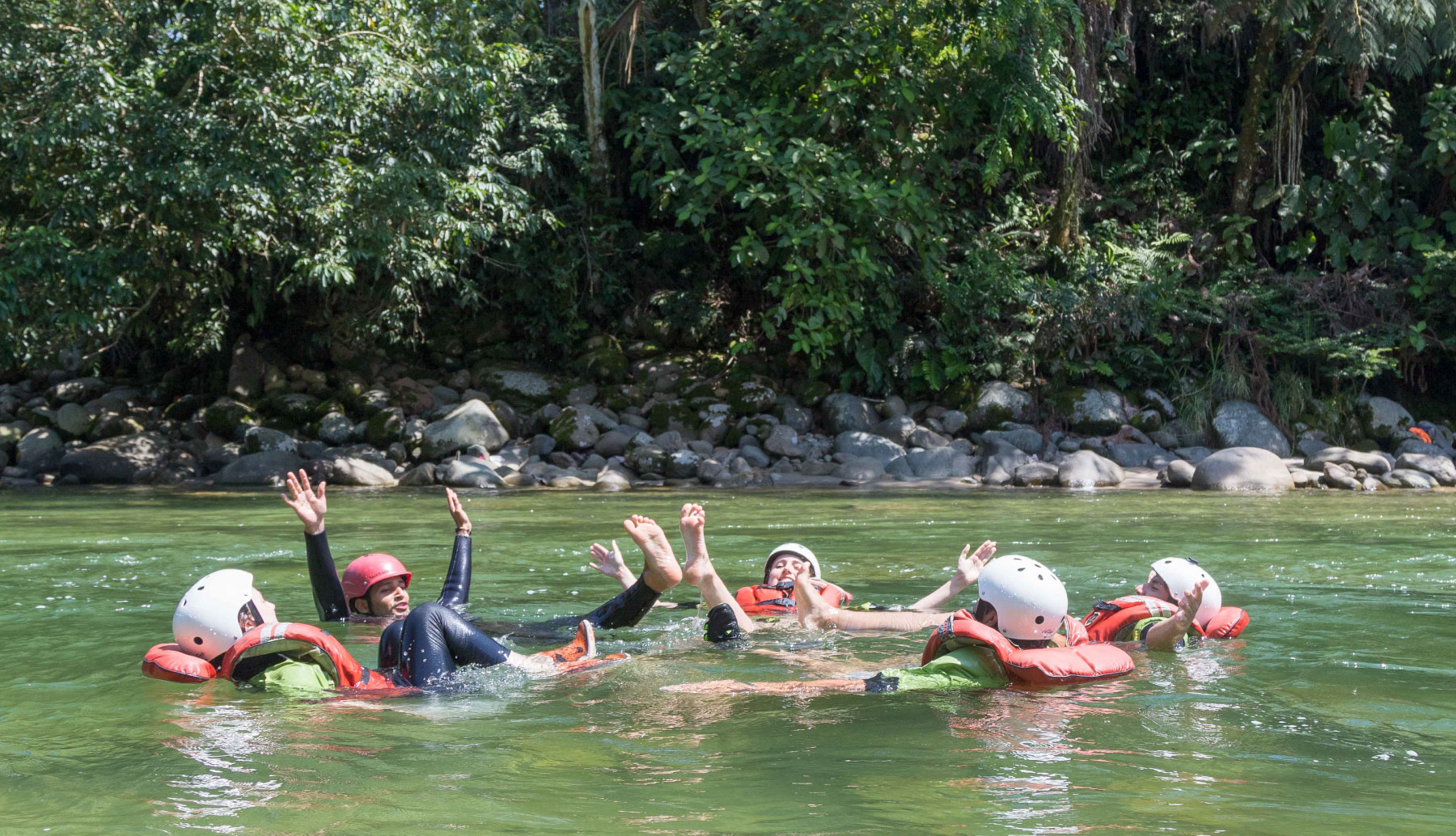 People in a river floating and swimming