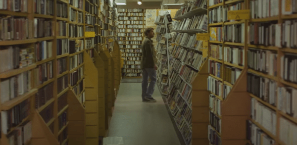 Man wandering the isles of a video store in Beyond the Gates