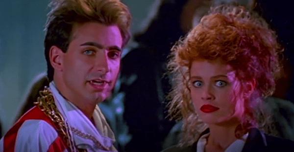 Rockin' vampire and a redheaded woman look at the camera in Rockula