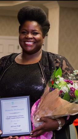 Octavia McDougle holding flowers and plaque of appreciation