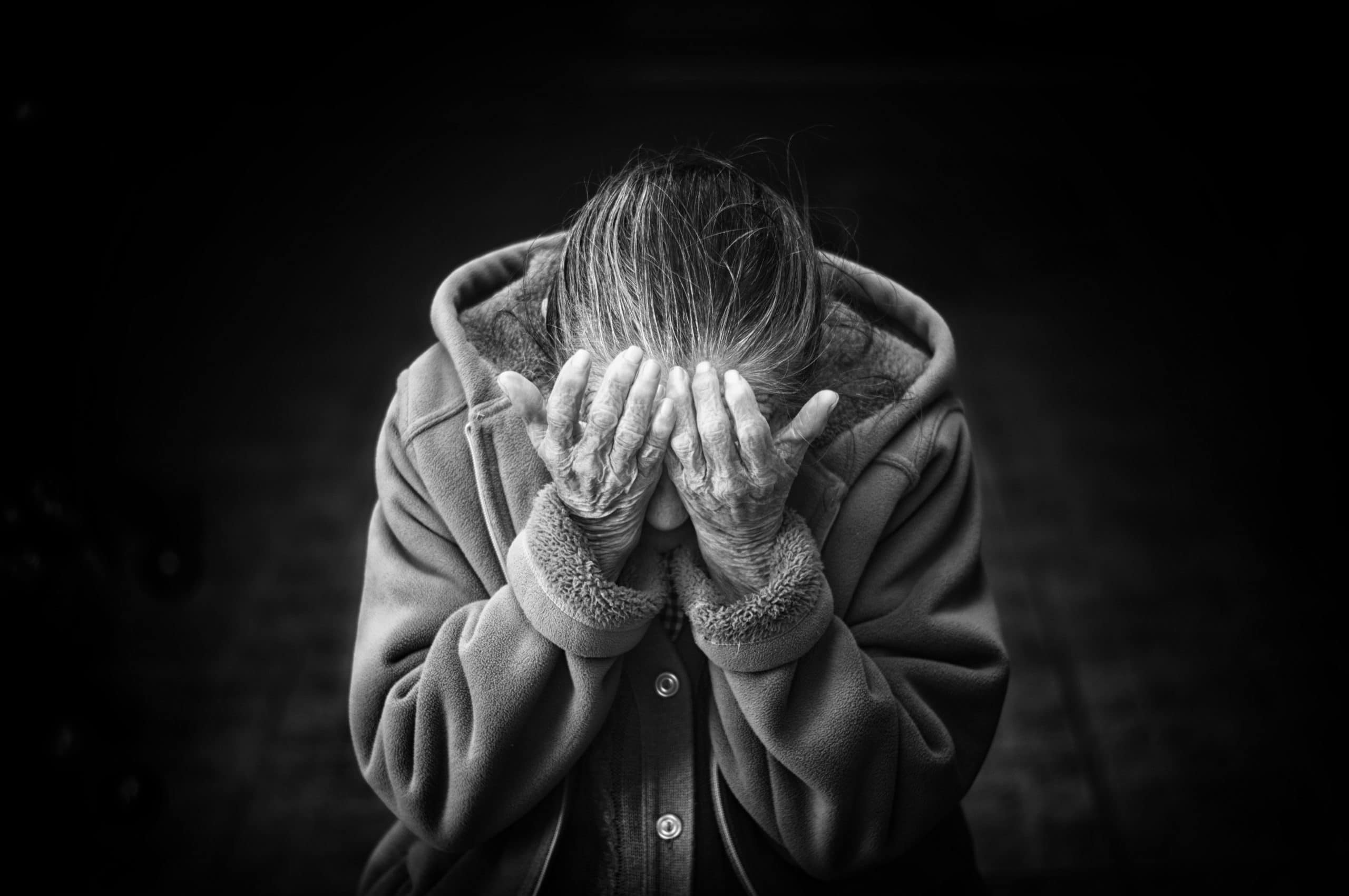 black and white picture of Elderly woman with hands on her face, upset