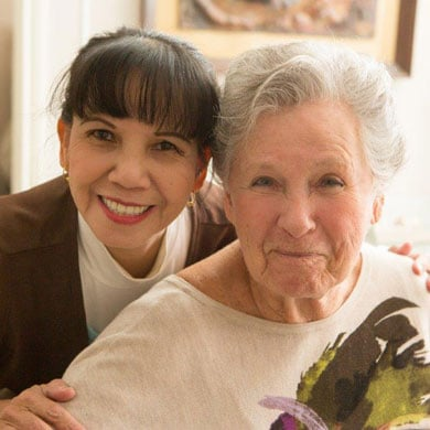 Caregiver with client smiling at camera