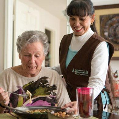 Caregiver serving dinner to client