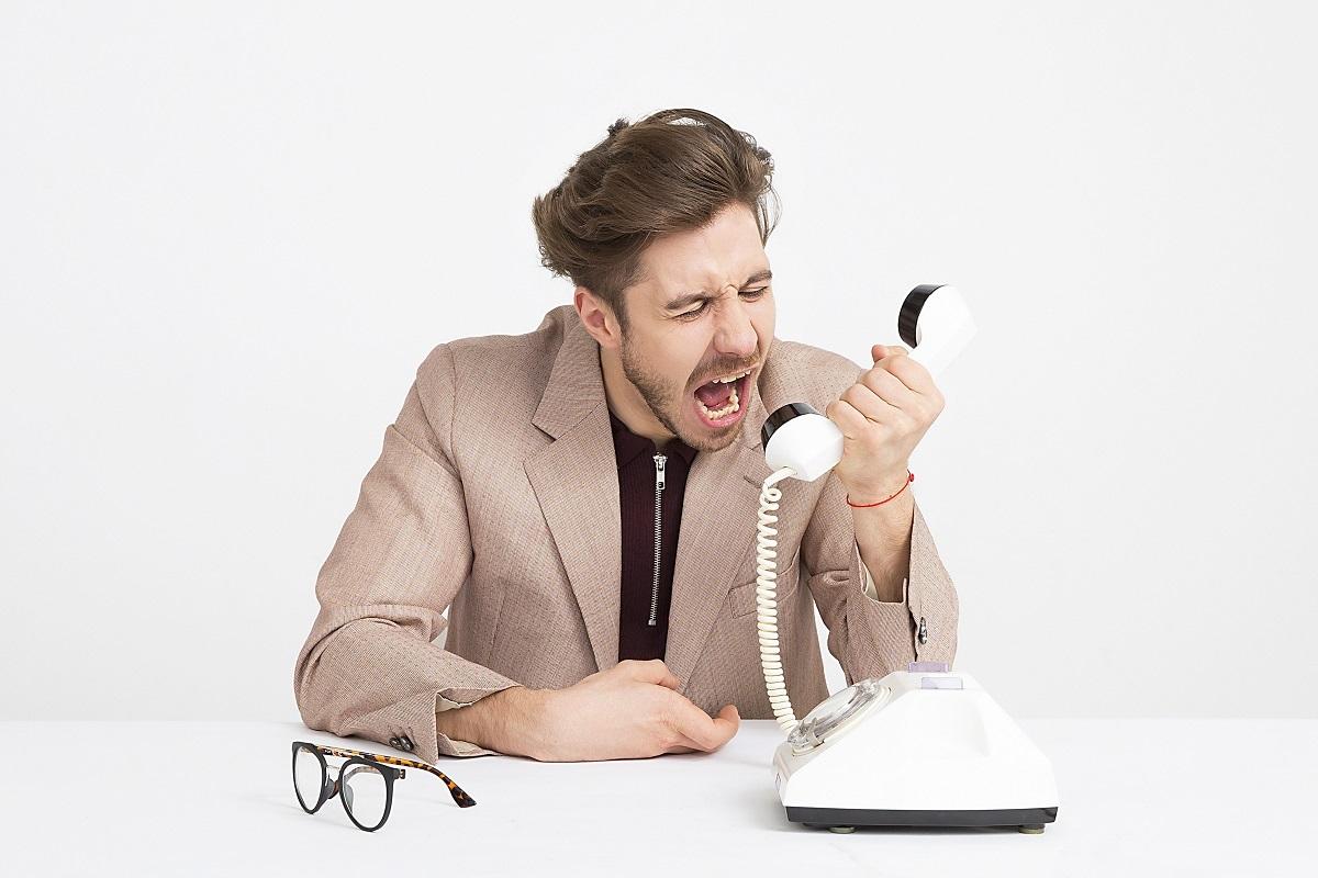 Homem gritando ao telefone e oferecendo um mau atendimento
