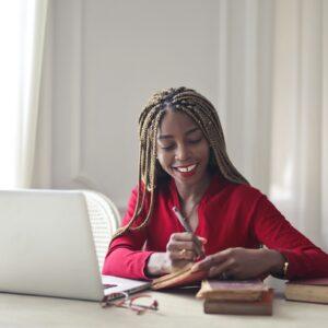 Mulher em frente a computador e livros