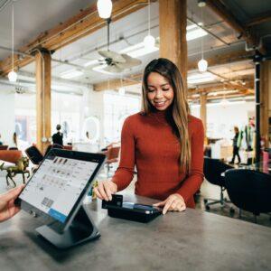 Mulher passando o cartão de crédito para pagamento em um estabelecimento