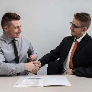 Dois homens se cumprimentando e fazendo fidelização de clientes