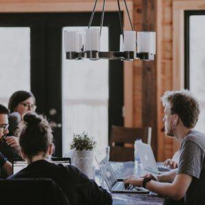 Equipe trabalhando em volta de uma mesa com seus computadores e headsets