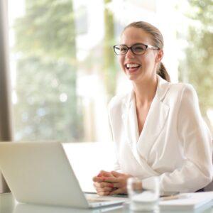 vendedora sorrindo em frente a um notebook