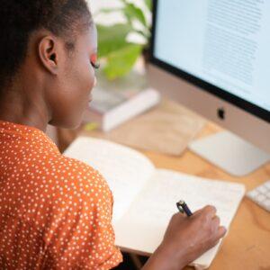 Mulher escrevendo em seu caderno em cima de uma mesa