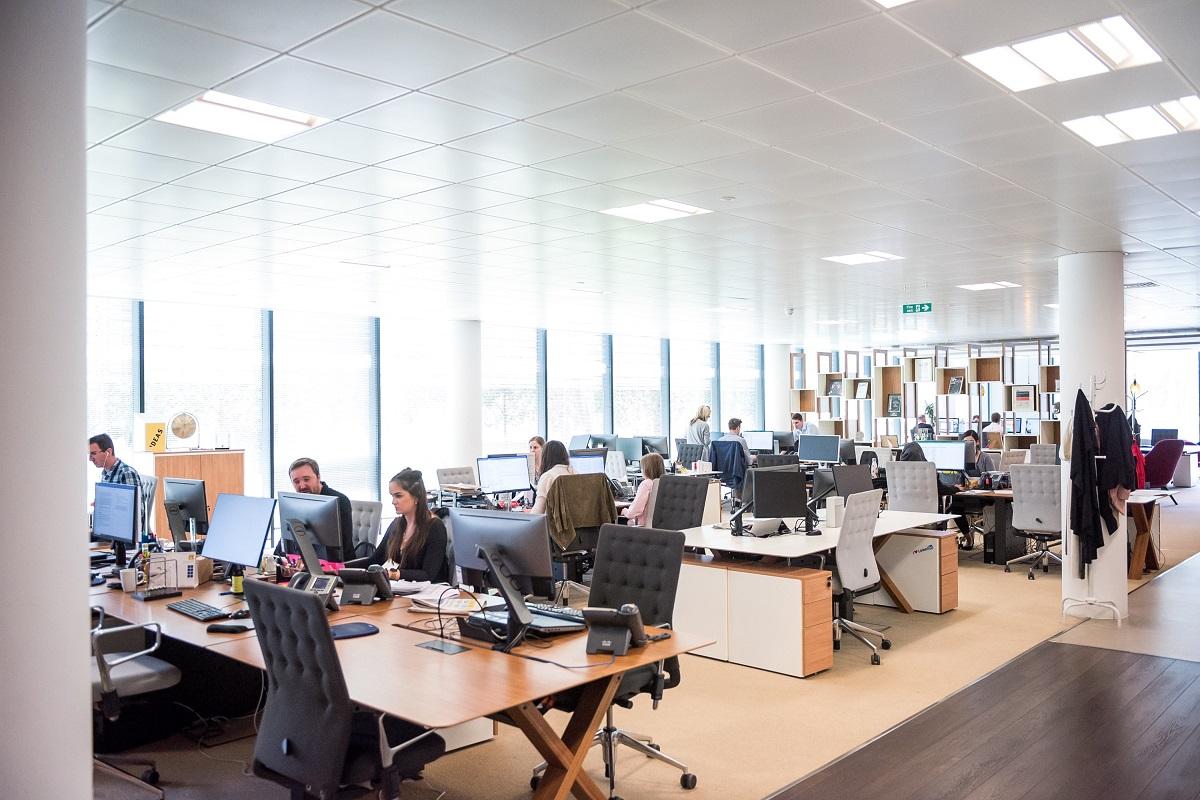 Sala com funcionários sentados em suas mesas, computadores e telefones