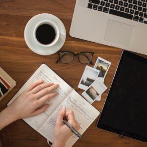 Mãos de uma pessoa escrevendo em um caderno junto a notebook e livros