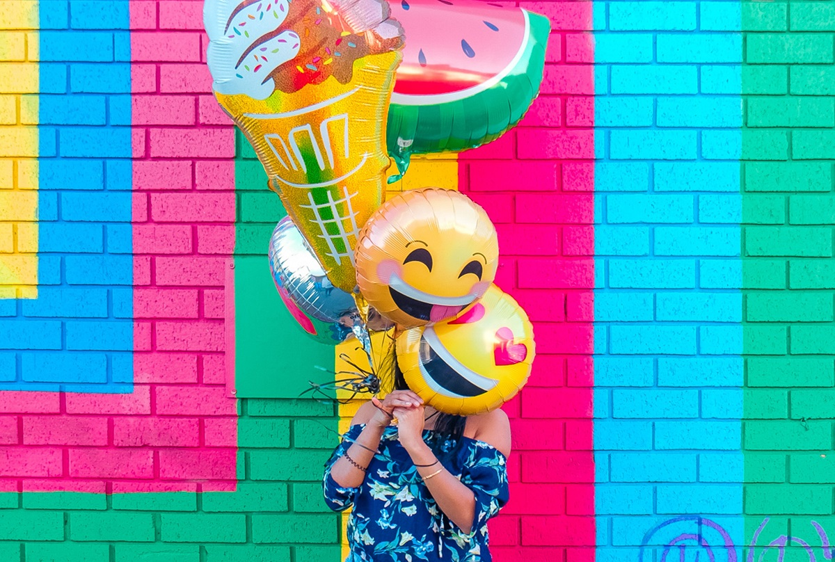 Pessoa com diversos balões com temáticas de carinha feliz e frutas nas mãos