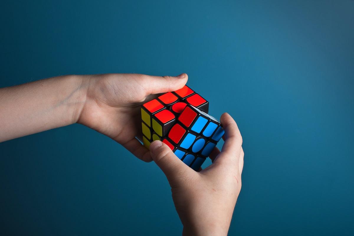 pessoa tentando resolver um cubo mágico