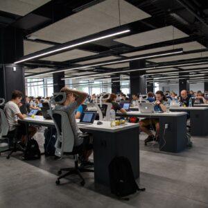 Escritório com diversos atendentes em suas mesas com seus computadores