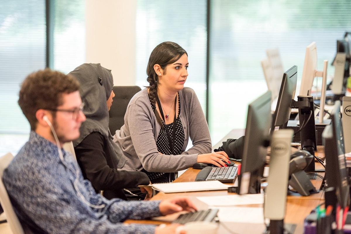 Três pessoas em frente a seus computadores