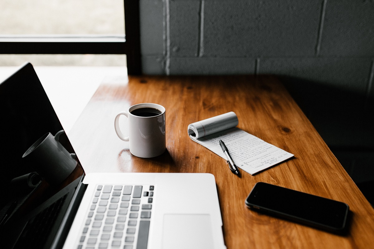 Papel, caneta, caneca, celular e notebook em cima da mesa