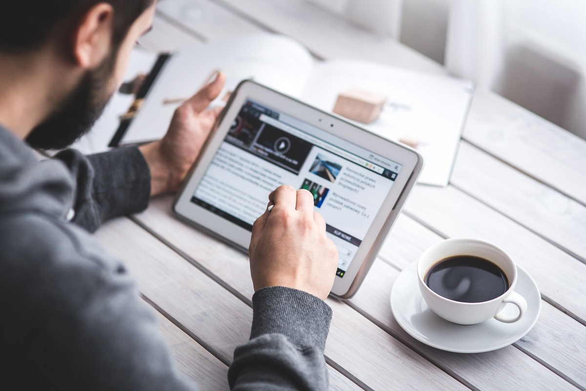 Pessoa usando um tablet ao lado de uma xícara de café