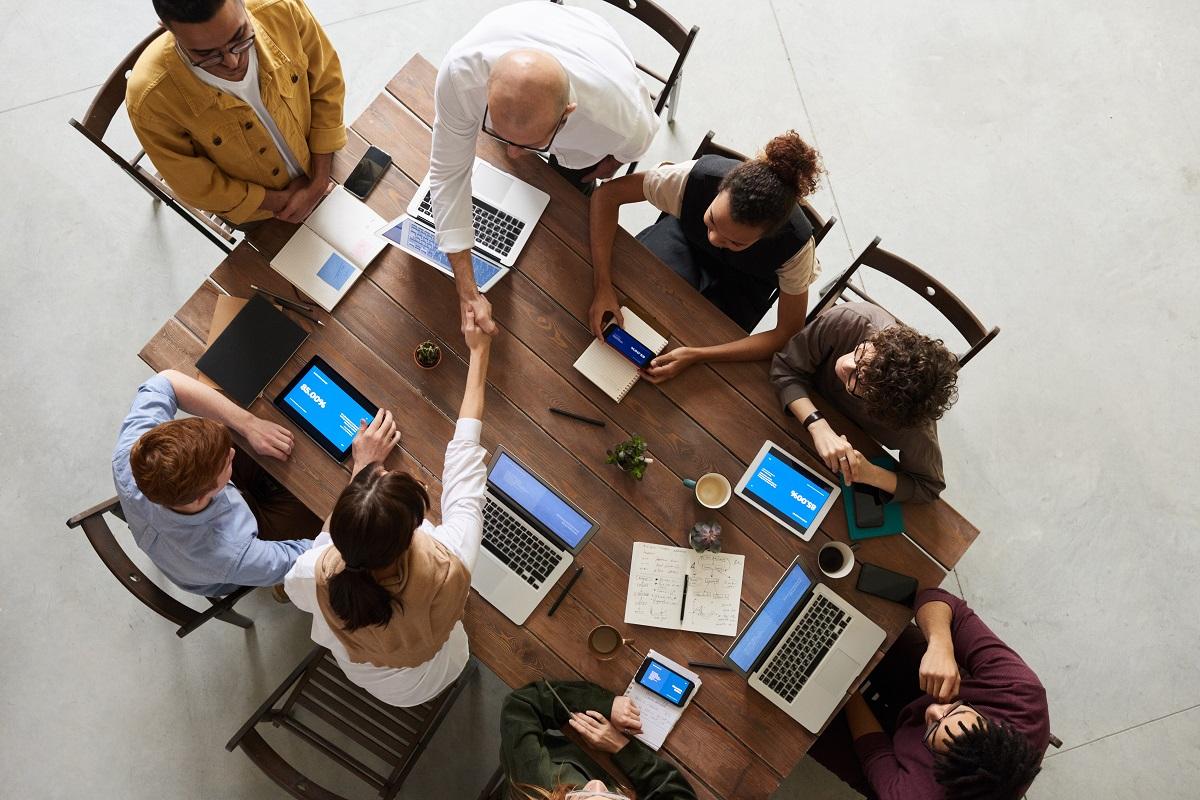 Pessoas com computadores ao redor de uma mesa enquanto duas delas se cumprimentam com um aperto de mãos
