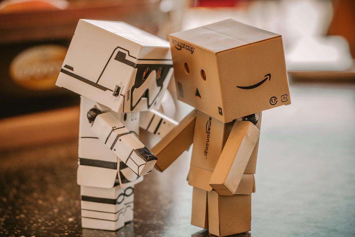 Dois robôs feitos de papelão dando um aperto de mãos