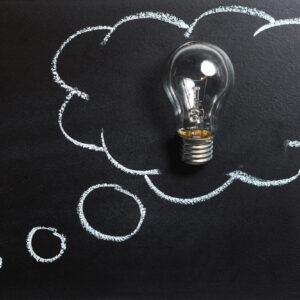 Desenho de um balão de pensamento feito com giz e uma lâmpada apagada dentro