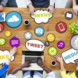pessoas em volta de uma mesa discutindo redes sociais