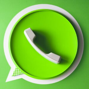 Simbolo do WhatsApp feito com telefone real e um balão de conversa de papel