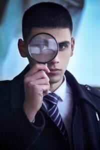Homem segurando uma lupa em frente ao olho direito