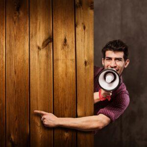 Homem com um megafone na mão e apontando para um muro de madeira com a outra mão