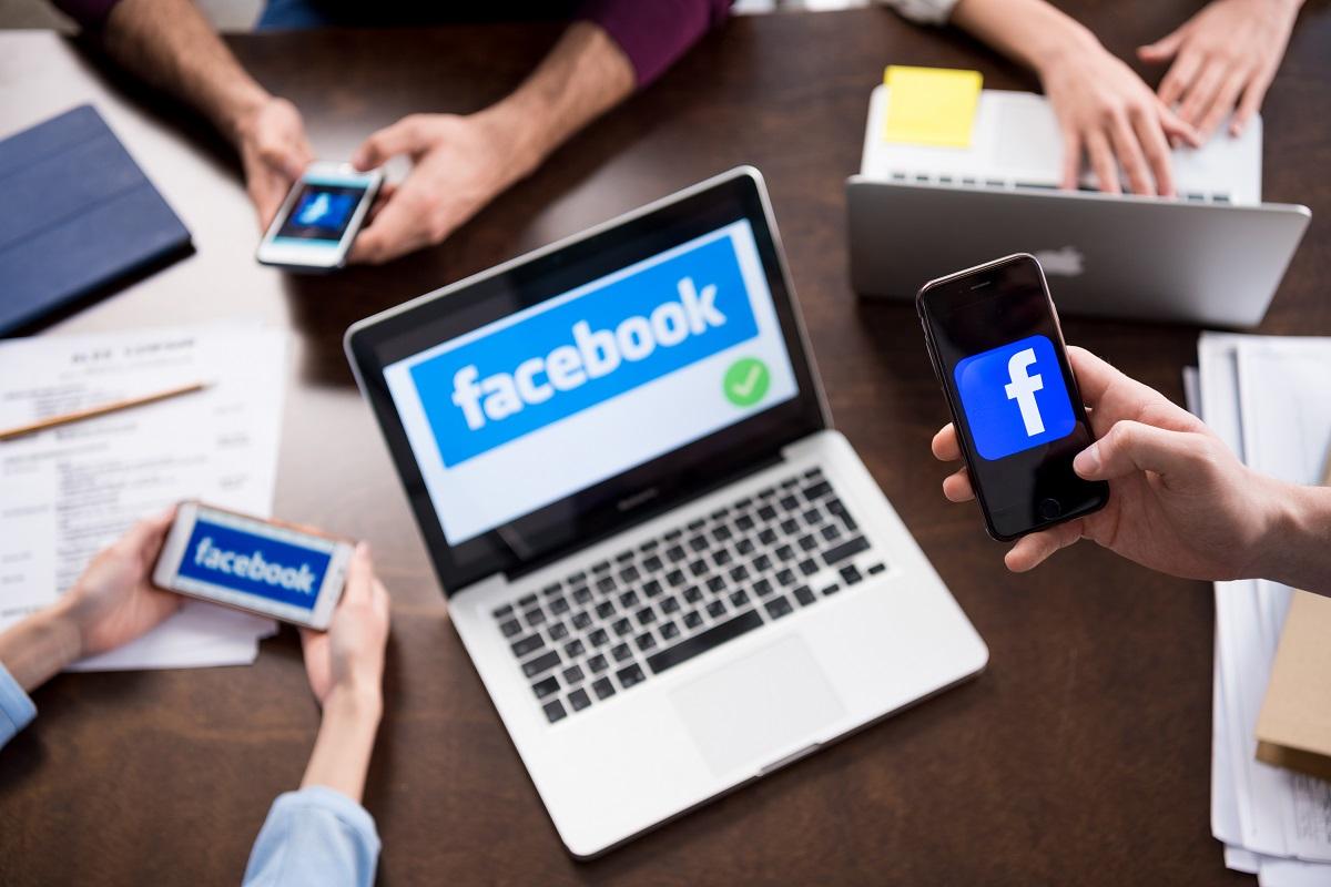 Pessoas utilizando notebooks e celular para vender pelo facebook