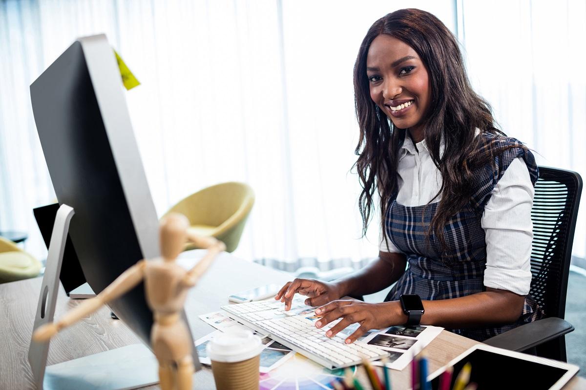 Mulher de negócios sorrindo em frente ao computador