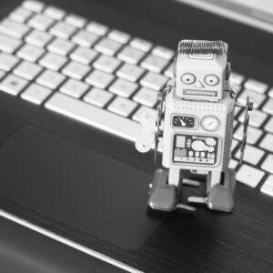 Robô na frente de um teclado; simbolo de chatbot de atendimento