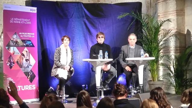Légende : Régine Brichet, secrétaire départementale déléguée à l'éducation et Jean Maurice Belayche, partenaire de l'opération accompagnent Thomas Dutronc sur scène lors de l'échange entre l'artiste et les collégiens.