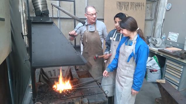 Un bénévole enseignant à deux enfants le métier de forgeron.