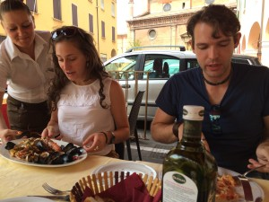 Jeannine with seafood pasta, Jason with pizza with french fries on it, Nicola's Pizzeria Ristorante, Bologna, Photo: Julie Santini