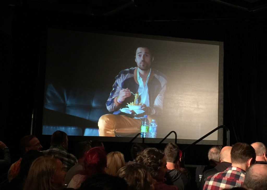 Brett Dalton gets a poutine delivered to him on stage after saying he'd like to try one (Photo by Jean-Frédéric Vachon)